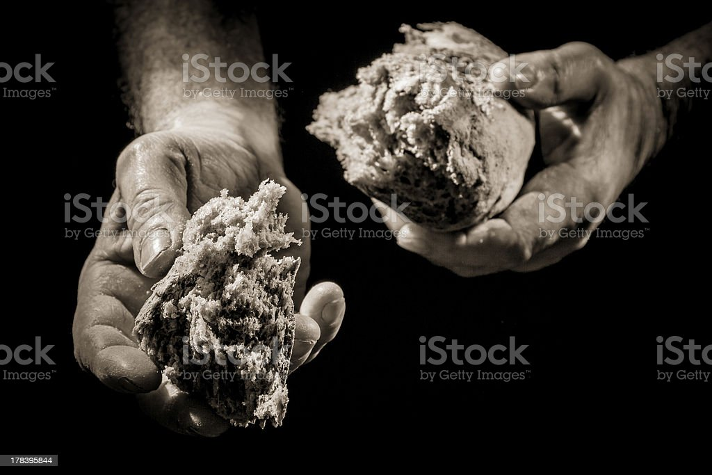 Human Hand giving a piece of bread stock photo