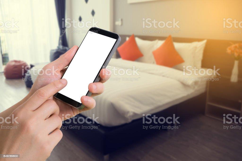 human hand hold smartphone on blurry modern bedroom - Photo