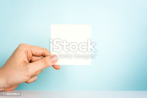 istock Human hand holding a beige blank note on the office desk and blue background. Design announcement message concept at work. 1136358820