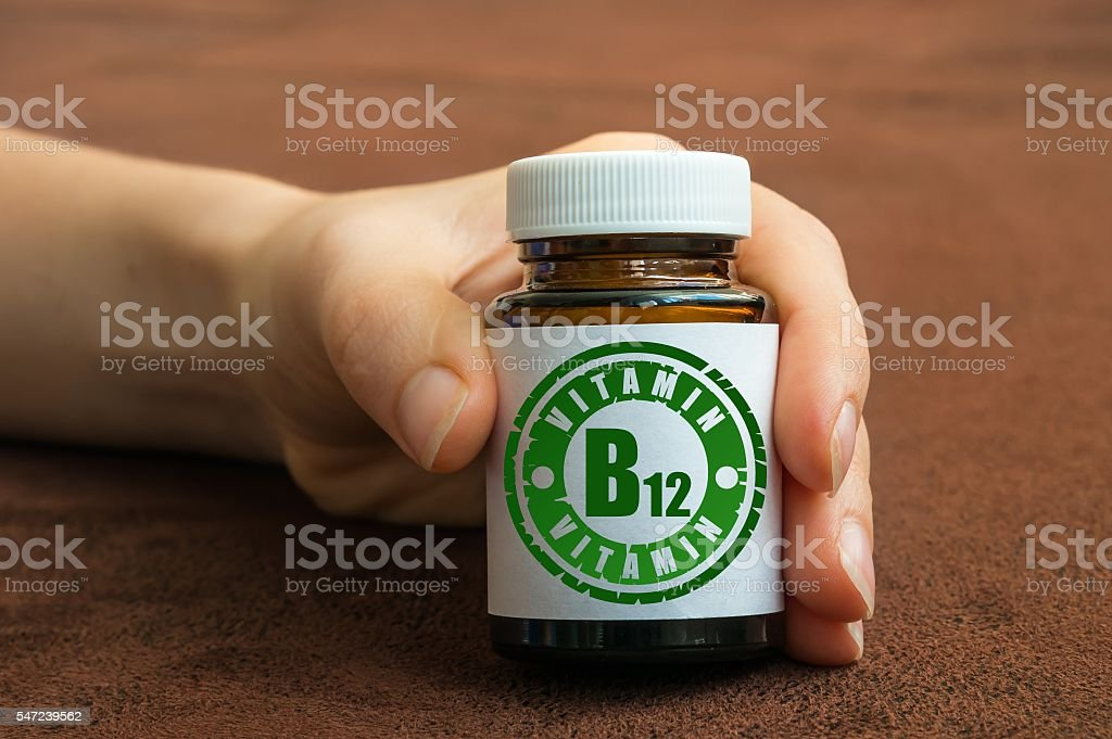 Human hand holding a bottle of pills with vitamin B12 stock photo