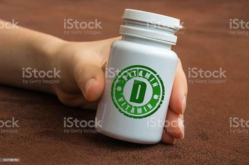 Human hand holding a bottle of pills with vitamin D stock photo
