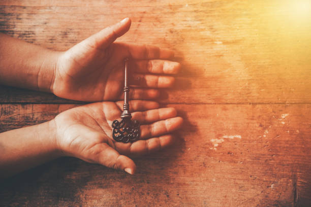 human hand holding a key - key stock pictures, royalty-free photos & images