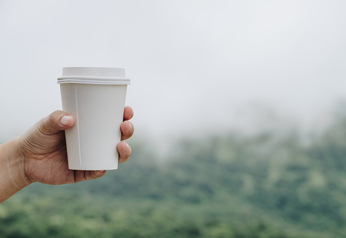 Human hand holding a paper cup of hot coffee with the nature background.