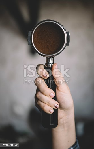 istock Human hand holding a portafilter with freshly ground morning coffee 528280178