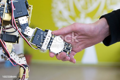 istock Human hand holding a robot hand with a handshake 1002338444