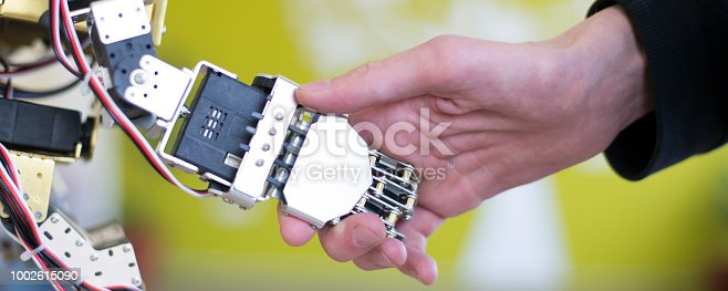 istock Human hand holding a robot hand with a handshake 1002615090