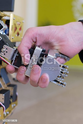 istock Human hand holding a robot hand with a handshake 1002615826