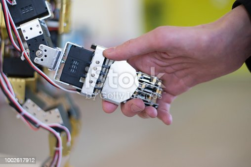istock Human hand holding a robot hand with a handshake 1002617912