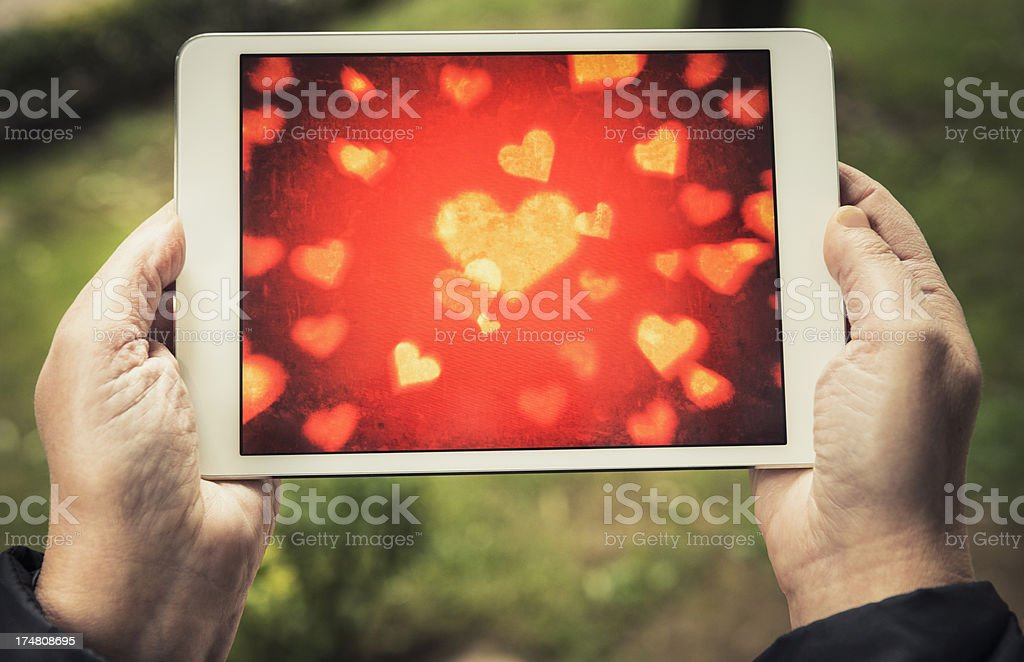 Human hand holding a small digital tablet with black screen royalty-free stock photo
