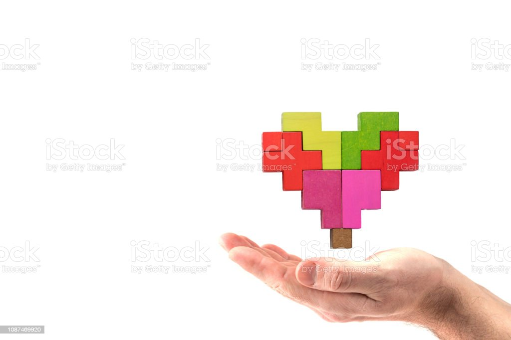 Human hand holding abstract heart. Human heart is made of multi-colored wooden blocks. stock photo