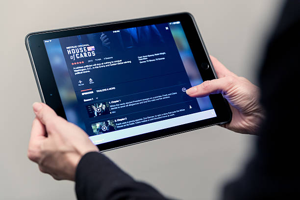 Human Hand Holding Apple ipad with Netflix Application Laval, Canada - November 30, 2016: Human Hand Holding Apple iPad with Netflix Application with the latest download movies and shows option released on November 30th 2016. netflix stock pictures, royalty-free photos & images