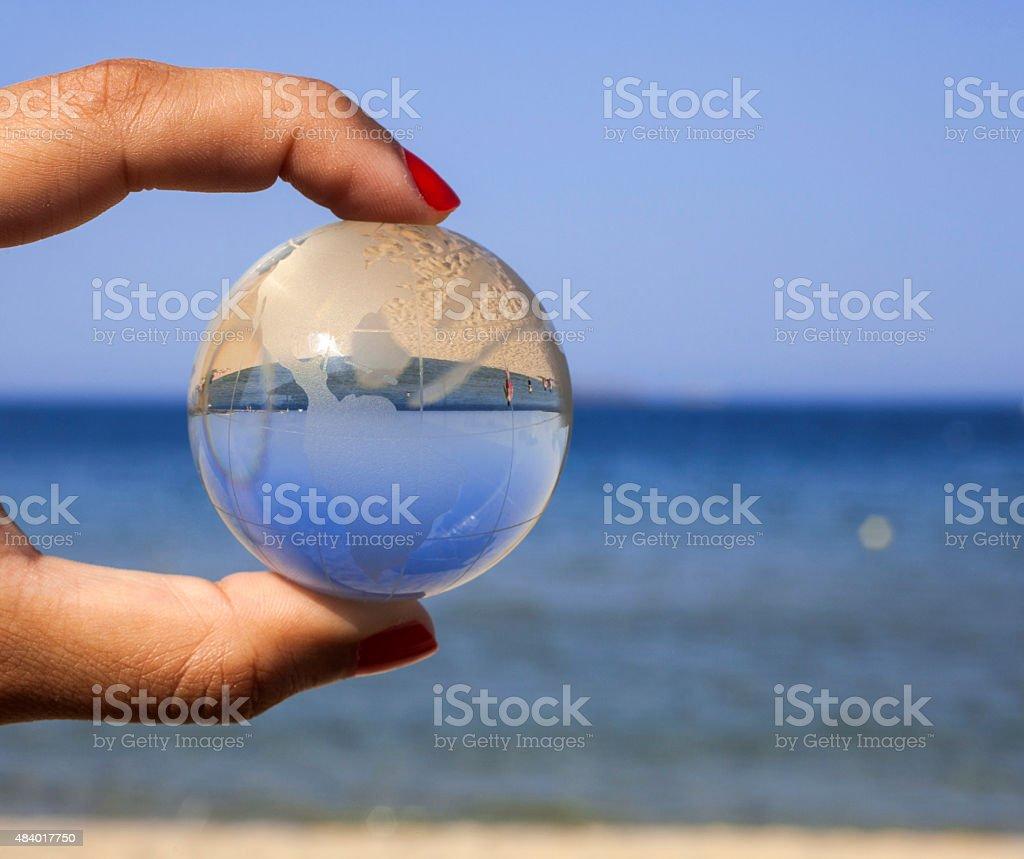 Human hand holding crystal globe. stock photo