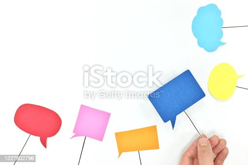 812513444 istock photo Human hand holding different colors speech bubbles. Business teamwork, communication, brainstorming, collaboration and freedom of speech concept. 1227602796