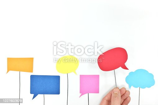 812513444 istock photo Human hand holding different colors speech bubbles. Business teamwork, communication, brainstorming, collaboration and freedom of speech concept. 1227602829