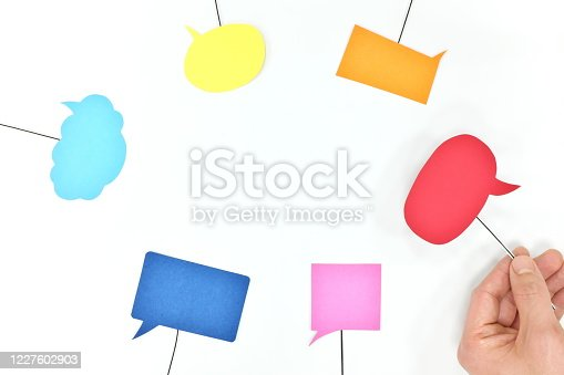 812513444 istock photo Human hand holding different colors speech bubbles. Business teamwork, communication, brainstorming, collaboration and freedom of speech concept. 1227602903