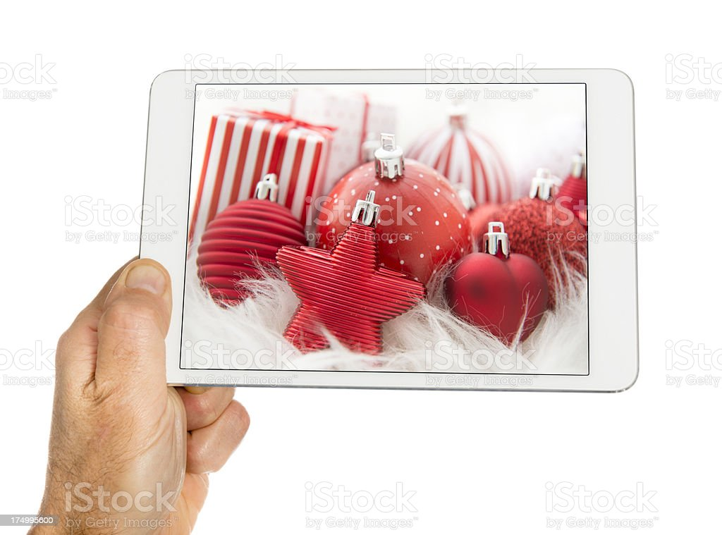 Human hand holding digital tablet with christmas decoration royalty-free stock photo
