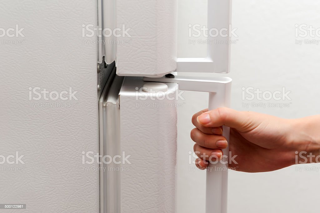 Human hand holding fridge door isolated on white background stock photo