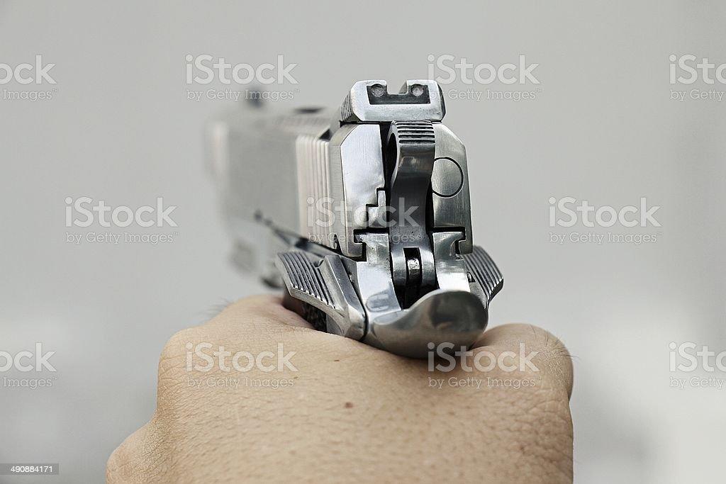 Human hand holding gun, hand aiming a handgun, .45 pistol. stock photo