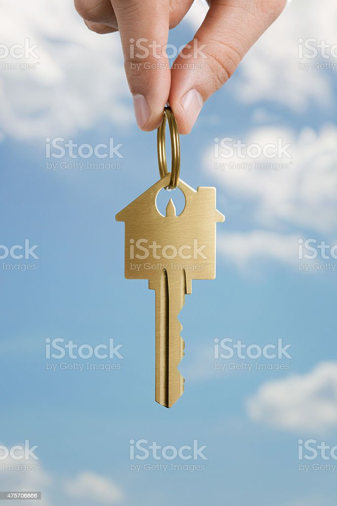 Human hand holding house shaped key stock photo