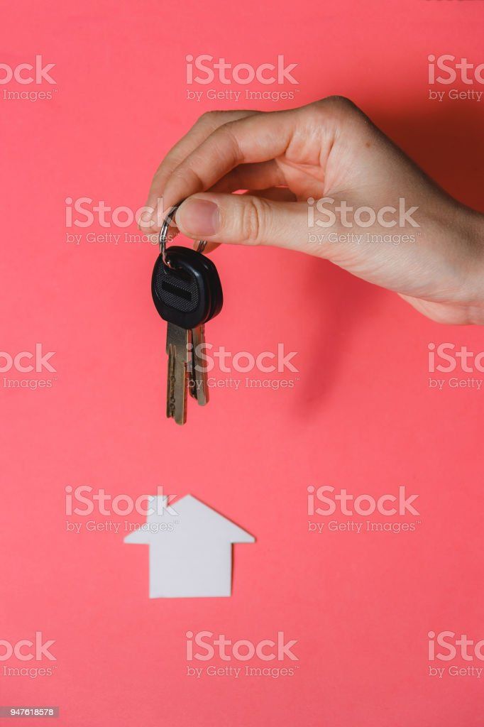 Human Hand Holding Key to Dream Started House against Pink Background. stock photo