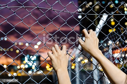 Human hand holding on wire fence at night.