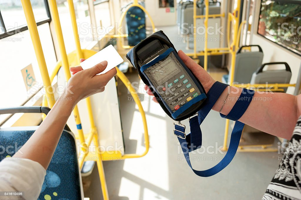 Human hand holding plastic cards. Passenger pays for fare in stock photo