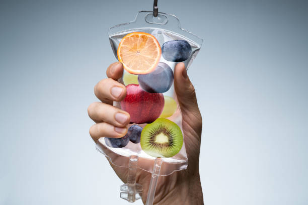 Human Hand Holding Saline Bag With Fruit Slices Over Grey Background stock photo