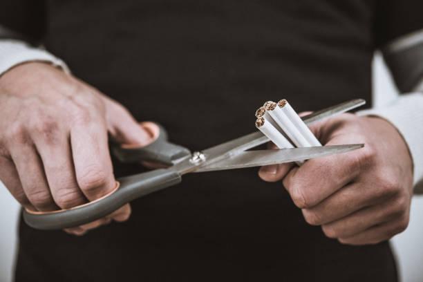 Human hand holding scissors around cigarettes stock photo
