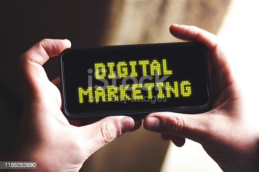 istock human hand holding smart phone with text, digital marketing 1155252690