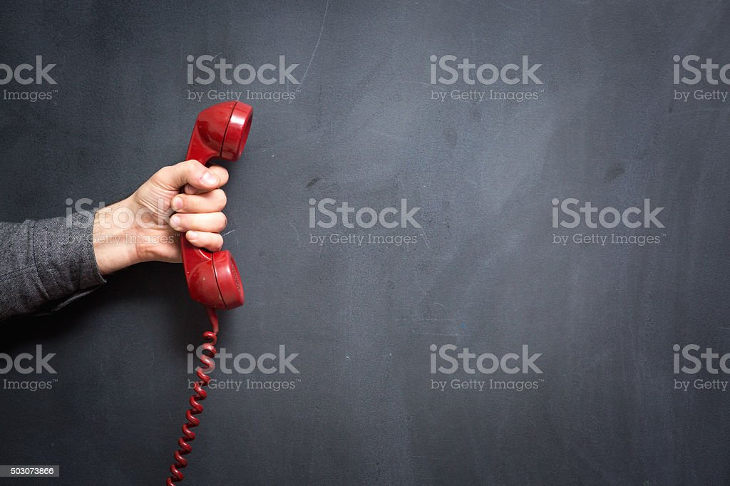 Human hand holding telephone on blackboard - Contact Us stock photo