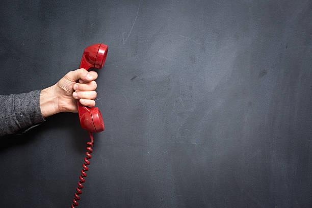 mano umana che tiene il telefono su lavagna-contatti - cornetta telefono foto e immagini stock