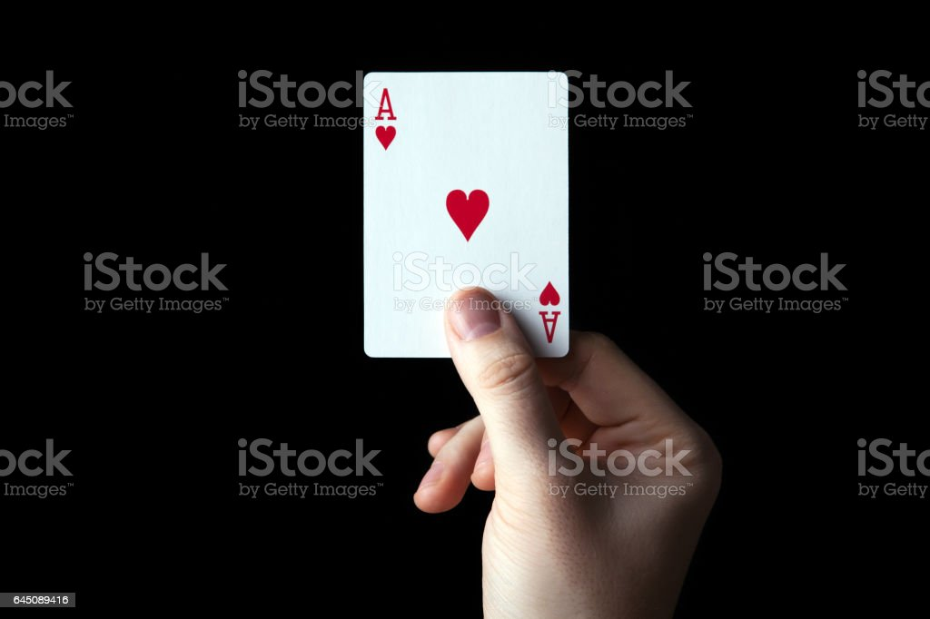 human hand holding the ace of hearts stock photo
