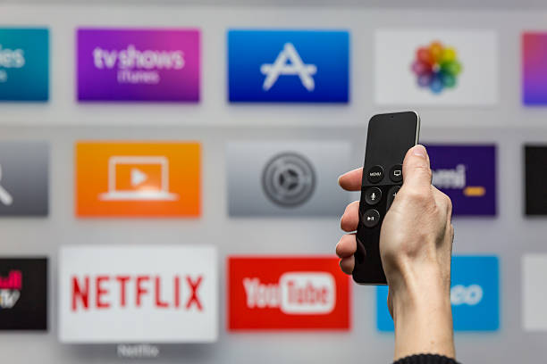 Human Hand Holding The New Apple Tv Siri Remote Montreal, Сanada - November 22, 2015: Human hand holding The 4th generation Apple TV new Siri remote browsing the channel selections. The Apple TV is produced by Apple Inc. netflix stock pictures, royalty-free photos & images
