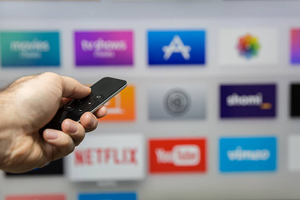 Human Hand Holding The New Apple Tv Siri Remote Montreal, Сanada - January 3, 2016: Human hand holding The 4th generation Apple TV new Siri remote browsing the channel selections. The Apple TV is produced by Apple Inc. netflix stock pictures, royalty-free photos & images