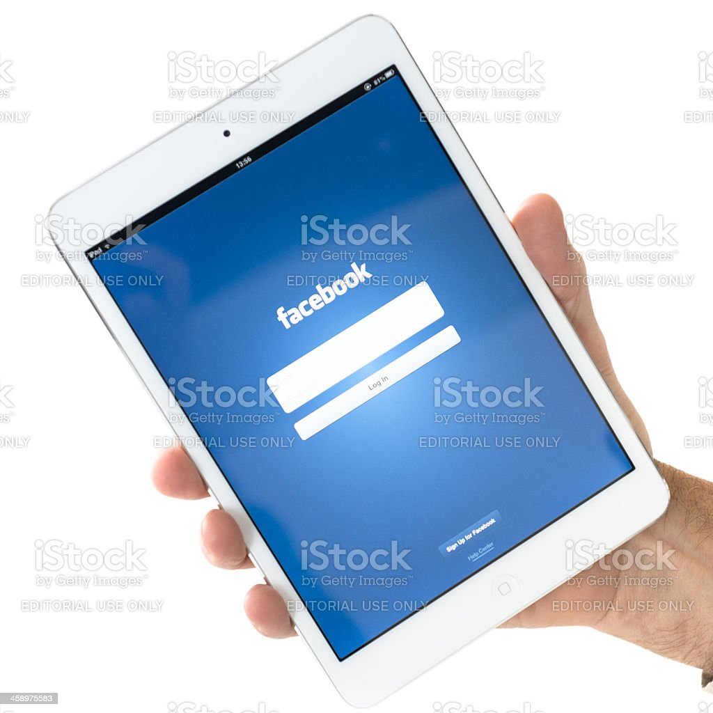 Human hand holding the new Ipad Mini with facebook.com app royalty-free stock photo