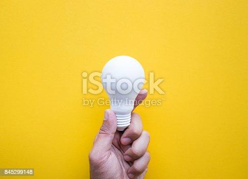 845301446 istock photo Human hand holding white lightbulb on pastel color 845299148