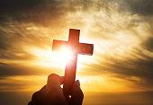 Human hand holding wooden cross.