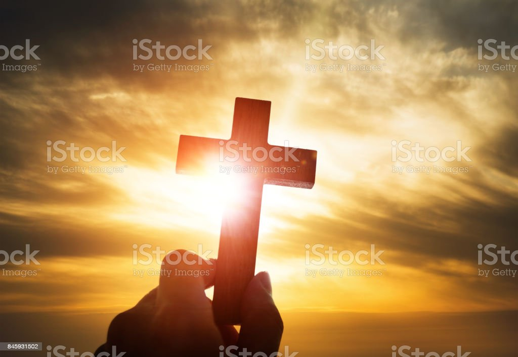 Human hand holding wooden cross stock photo