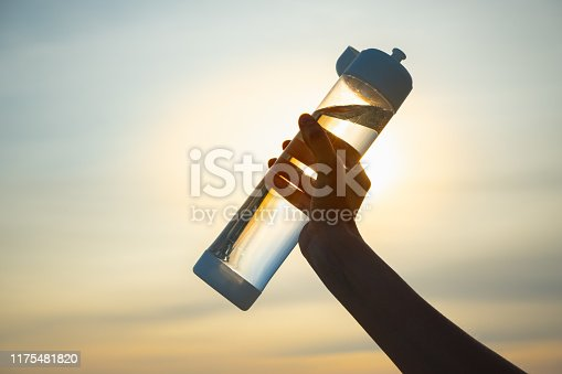 Close up of a reusable water bottle in a human hand, concept of thirst, rehydration and decreasing single use plastic