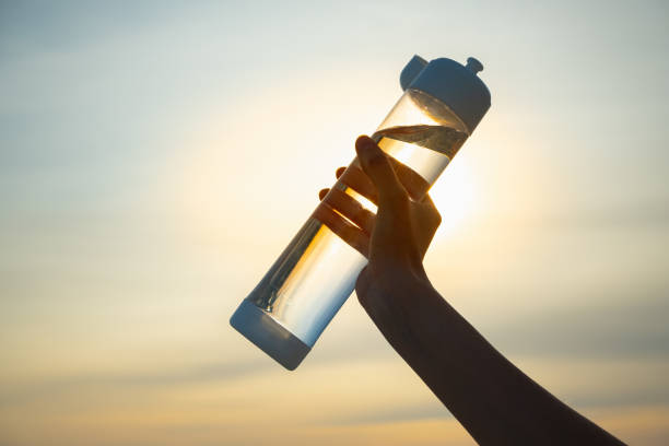 Human hand holds a water bottle against the setting sun. stock photo