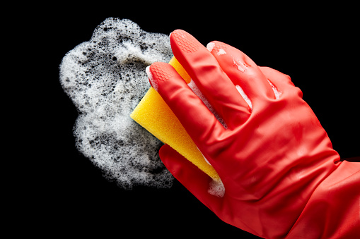 istock Human hand in a red rubber glove wiping with a sponge on isolated black background 1222801675