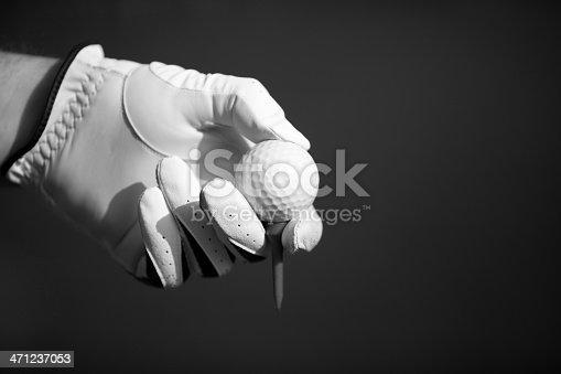 Human hand in golf glove holding ball