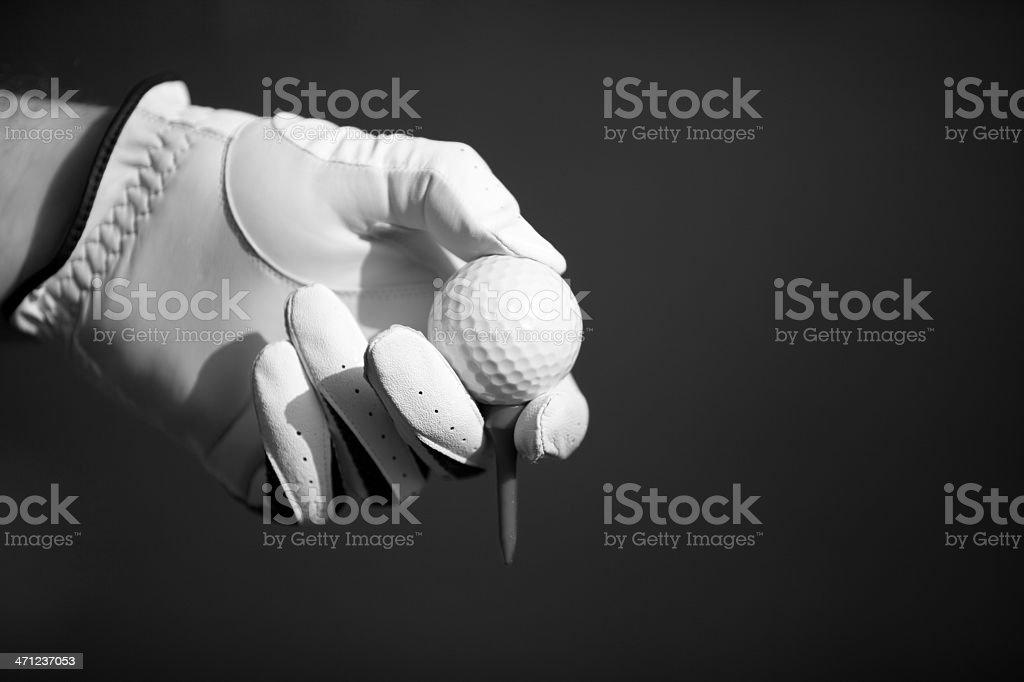 Human hand in golf glove holding ball stock photo