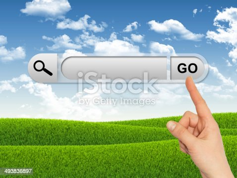 Human hand indicates the search bar in browser. Field of grass and blue sky as backdrop