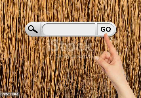 Human hand indicates the search bar in browser. Yellow dry grass surface on background