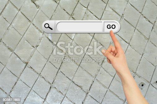 Human hand indicates the search bar in browser. Aged brown cemented floor on background