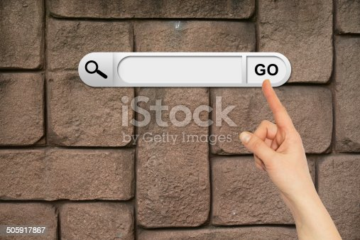 Human hand indicates the search bar in browser. Wall of brown bricks on background