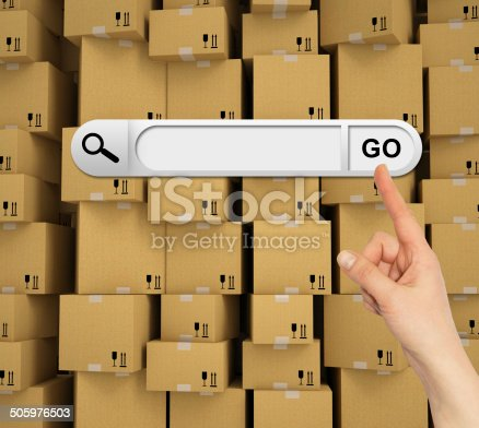 Human hand indicates the search bar in browser. Wall of cardboard box as backdrop