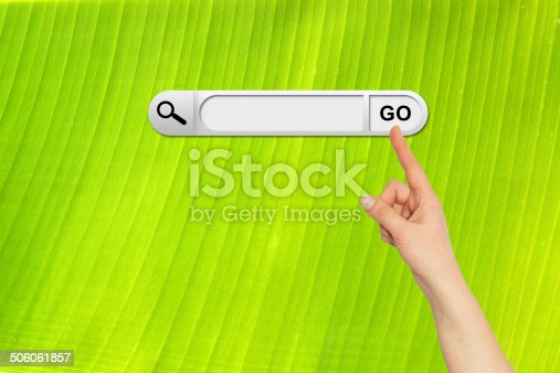 Human hand indicates the search bar in browser. Backlit fresh green palm leaf on background