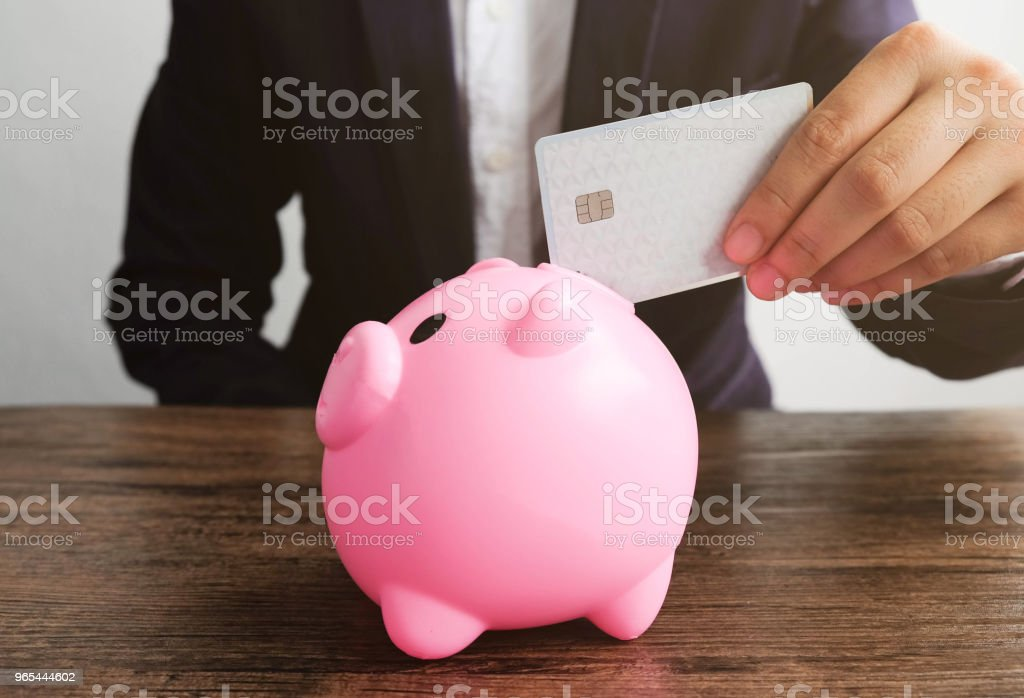 Human hand insert credit card in to piggy bank zbiór zdjęć royalty-free